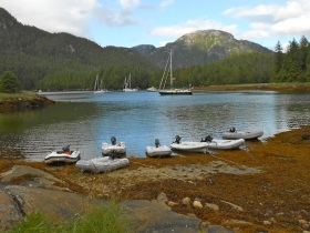 The Sail Alaska fleet anchored in Lowe Inlet, and dinghys lined up at the cookout cove on the 4th of July